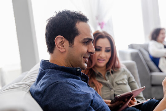 Couple looking at digital tablet on sofa