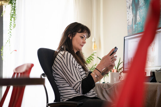 Mature woman working from home using phone