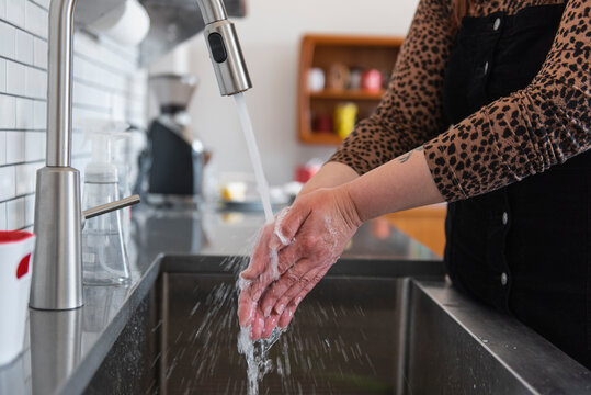 Woman washing hands in kitchen sink