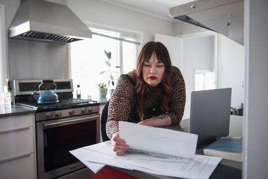 Mature woman reading document in kitchen