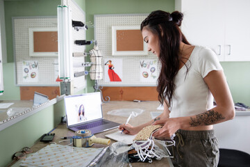 Young e-commerce seamstress making COVID-19 face masks in workshop
