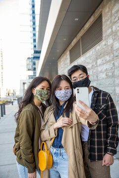 Brother and sisters in face masks using smart phone