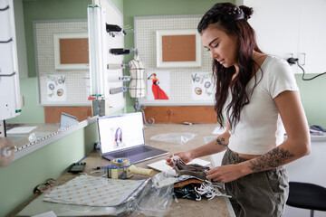 Young female e-commerce seamstress making COVID-19 face masks