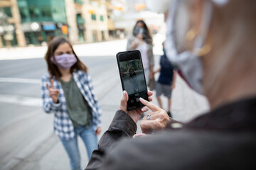 Grandmother with smart phone photographing granddaughter in face mask