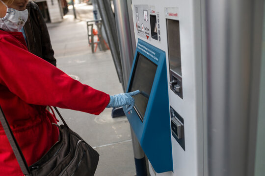 Senior woman in face mask and gloves using ATM