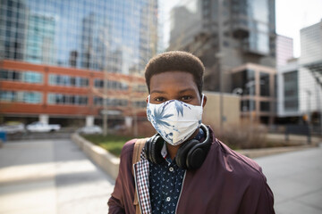 Portrait confident young man in face mask in sunny city