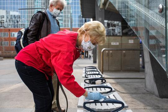 Senior woman in face mask sanitizing city bench