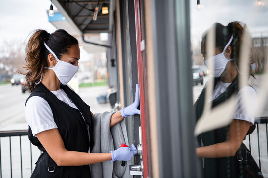 Female business owner in gloves and face mask locking cafe door