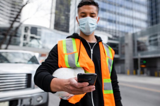 Male construction worker in face mask using smart phone in city