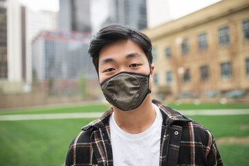 Portrait confident young man in face mask in city park