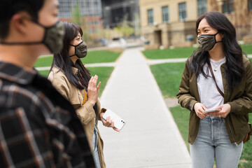 Brother and sisters in face masks in city park