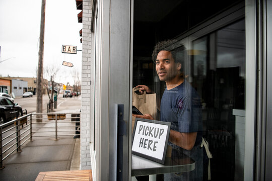 Male business owner ready with takeout food at cafe window