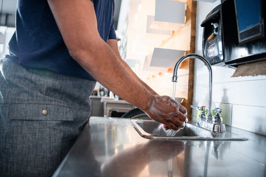 Waiter washing hands at sink in cafe