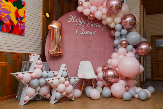 Beautiful festive decorations, pink and grey balloons arch, wooden stars, white chair and number one balloon on wooden round background. Little 1 year old girl birthday party photo zone.