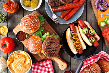 Photo sur Aluminium Pays d Europe Summer BBQ food table scene with hot dog and hamburger buffet. Top view over a dark wood background.