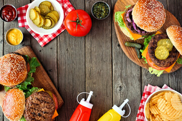 BBQ hamburger frame. Above view table scene view over a dark wood background. Copy space.