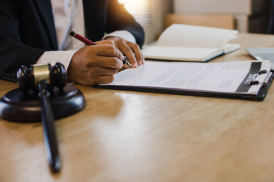 hand of business people sign contract with justice hummer on table