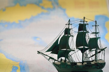 Vintage scale model of the historical tall ship and old white nautical chart close-up. Planning travel, sailing accessories, concept art, graphic resources, objects, collecting