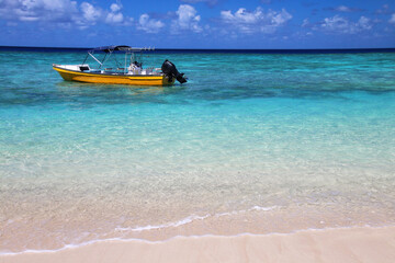 Tourist boat anchored at Gee island in Ouvea lagoon, Loyalty Islands, New Caledonia