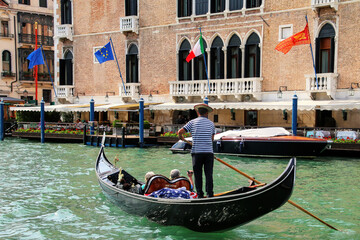 Gondolier rowing gondola with tourists on Grand Canal in Venice, Italy