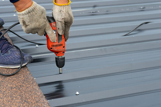 Workers installing the metal sheet roof by electrical drilling machine. Selective focus on the drilling tool while building the roof