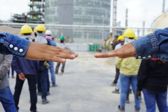 Hands of the workers unfolded to measure the distance during line up to safety talk or toolbox talk at Chemical plant in construction area. Corona virus epidemic. (Covid 19)