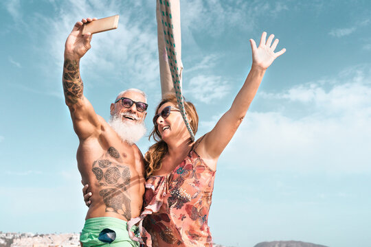Senior couple taking selfie with mobile smartphone on sailboat vacation - Happy mature people having fun celebrating wedding anniversary on boat trip - Love relationship and travel lifestyle concept