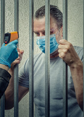 Measuring temperature with an infrared thermometer to a prisoner  in a mask standing behind jail bar