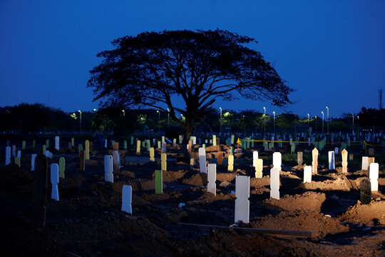 New graves are seen at dusk at a Muslim burial area provided by the government for victims of the coronavirus disease (COVID-19) at Tegal Alur cemetery complex in Jakarta