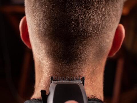 Men's haircut. get a haircut with a hair clipper close-up