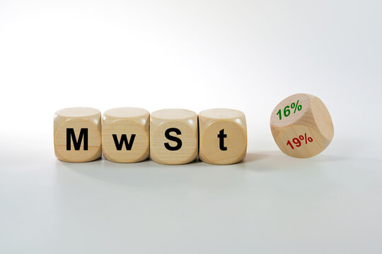 German economic stimulus package after the corona crisis lowers costs, MwSt (value added tax) written on wooden cubes, one dice turns from 19% to 16%, finance concept on a gray background