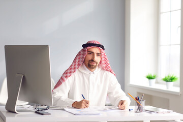 Calm arabian man sits at a table in the office. A