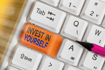 Text sign showing Invest In Yourself. Business photo showcasing Improve your Skills take courses Do masters Scholarship White pc keyboard with empty note paper above white key copy space