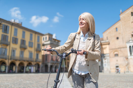 Smiling mature woman holding her bike in a big square