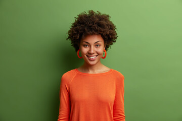 Portrait of beautiful dark skinned woman with bushy curly hair, smiles toothily, has optimistic...