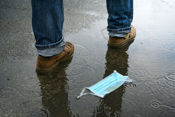 Man passes by after throwing away his face mask on the rainy street, but the danger of coronavirus...