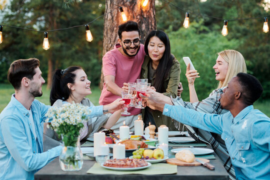 Group of intercultural cheerful friends gathered together by served table