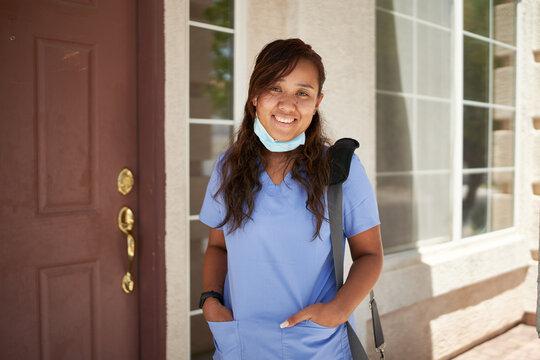 happy filipina nurse portrait in front of house