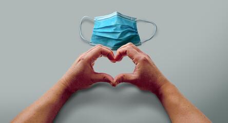 Manos formando un corazón para alentar a que el coronavirus se termine, usando sus mascarillas. Prevención