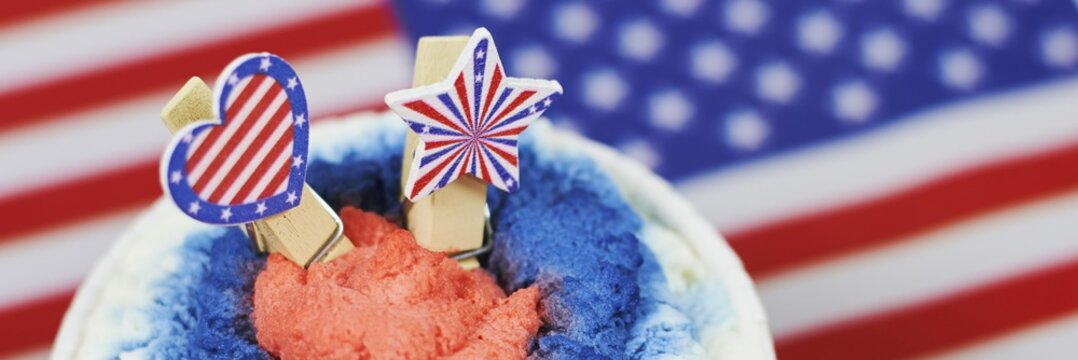 Soft focus of a colorful dessert with a blurry American flag in the background