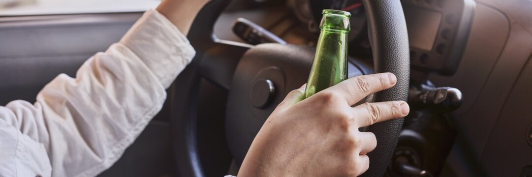 Bottle of beer in a man's hand behind the steering wheel - a concept of driving intoxicated