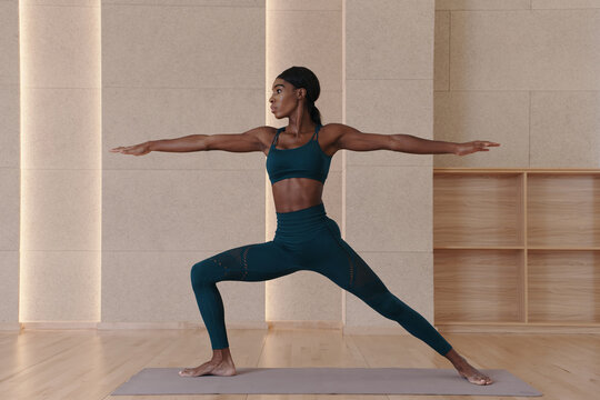 Young black woman practicing yoga, doing Virabhadrasana 2 exercise, Warrior two pose, indoor full length, studio background