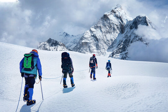 Group of climbers with backpacks on the glacier. Success, freedom and happiness, achievement in mountains. Climbing sport concept.