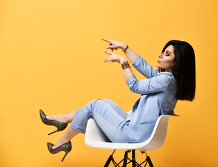 Young woman in official suit and high-heeled shoes sitting in an armchair pointing her fingers at...