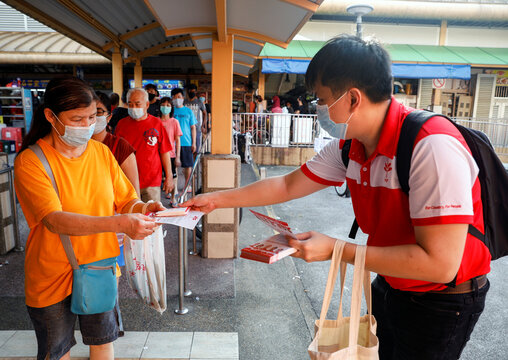A Progress Singapore Party (PSP) volunteer hands out leaflets at a food centre ahead of the general election in Singapore