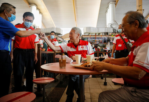 Lee Hsien Yang and Tan Cheng Bock of the Progress Singapore Party (PSP) have their breakfast before a walkabout ahead of the general election in Singapore