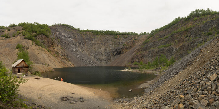 Artificially formed lake in a quarry for stone mining. Near the lake a wooden house. Big panoramic image