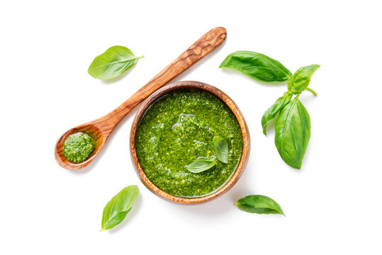 Traditional italian sauce pesto with green basil in wooden bowl isolated on white background