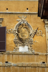 Coat of arms of noble families in wall on Piazza Tolomei in Siena. Italy