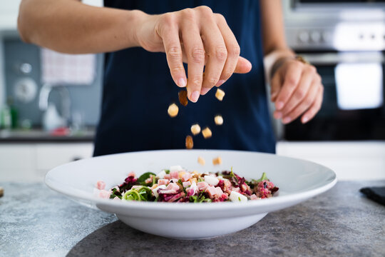 Woman Cooking Salad In Kitchen